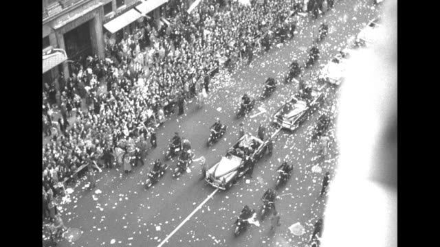 Various overhead shots of car carrying Gen Douglas MacArthur at front of motorcade stopped momentarily in front of church confetti flying through air...