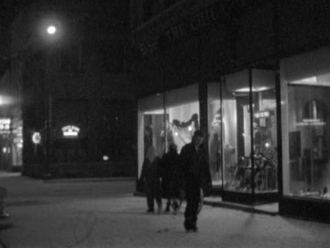 Various pedestrians in Winter attire walking on snow covered streets passing lit department store storefront mother boy window shopping BRIEF MS...