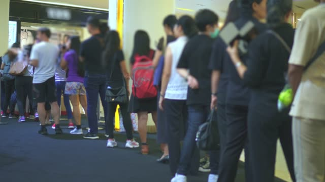 various people queueing / waiting in line - linea video stock e b–roll