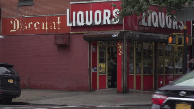 vidéos et rushes de various people walk past liquor store entrance as it rains down on brooklyn. - coin
