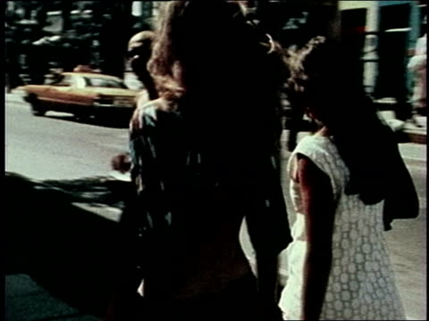 Various people walking down city streets / young women wearing shirts showing their midriff 1970s fashions on July 01 1971 in New York New York