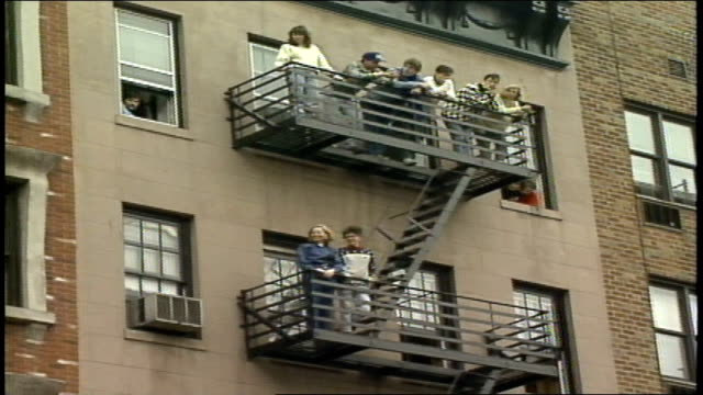 various people watching marathon from fire escapes - 非常階段点の映像素材/bロール