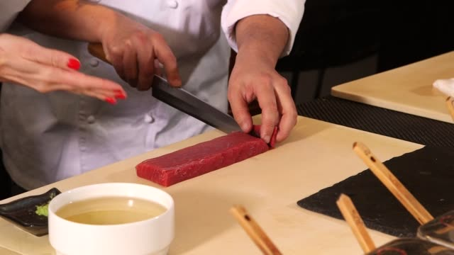 vidéos et rushes de various pieces of prepared raw fish being cut into pieces by a chef in sushi nakazawa restaurant in new york city, new york on march 24th, 2015... - sushi