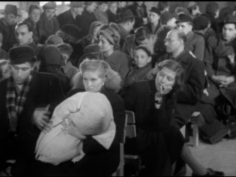 various refugees men women children families waiting in tempelhof airport vs refugees exiting terminal lobby elderly female being escorted out on... - flugpassagier stock-videos und b-roll-filmmaterial