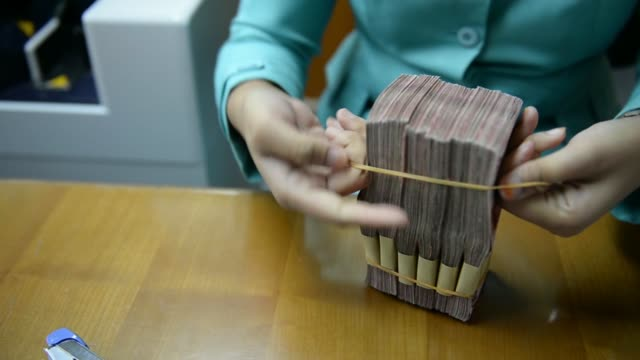 various shots a clerk arranges bundles of indonesian 100,000 rupiah banknotes and 50,000 rupiah banknotes on a desk at a currency exchange office in... - exchange rate stock videos & royalty-free footage