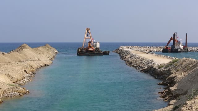 various shots a dredging pontoon operates offshore beyond pipe sections stored for use at the construction site for the northern cyprus water supply... - undersea stock videos & royalty-free footage
