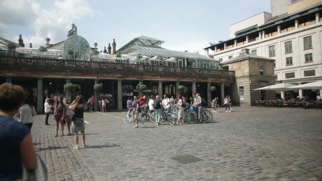 Various shots a group of tourists stand with rental bicycles in a square in front of Covent Garden Market in central London on Monday Aug 4 Tourists...