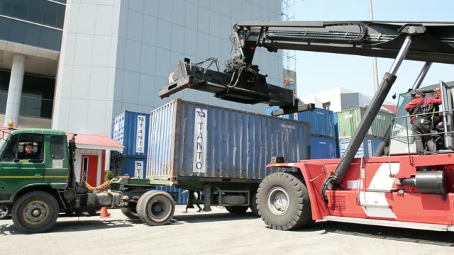 various shots a kalmar reachstacker loads shipping containers onto freight trucks at the tanjung priok port operated by state owned pt pelabuhan... - newly industrialized country stock videos and b-roll footage