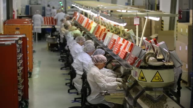 various shots a line of female workers box rodnye prostory candies as they move along a conveyor belt at the rossiya chocolate factory operated by... - chocolate milk stock videos & royalty-free footage