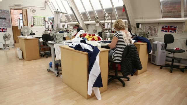 Various shots a worker arranges and passes material through the foot of a sewing machine as she sews a section of a Scottish St Andrews or Saltire...