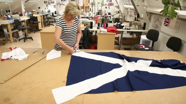 Various shots a worker trims and marks with a ruler white material from the edges of a Scottish St Andrews or Saltire flag during manufacture at the...
