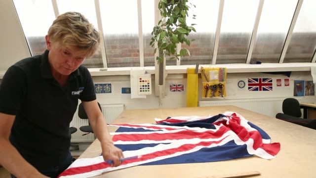 stockvideo's en b-roll-footage met various shots a worker trims with scissors and marks with a ruler excess material from the edges of a british union flag during manufacture at the... - alle vlaggen van europa