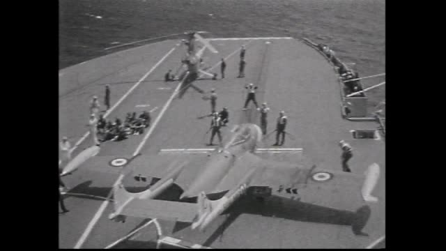 various shots aircraft carrier HMS Centaur sits in port / cutaway film cameraman anon / Royal Navy Helicopter C 977 takes off from the aircraft...