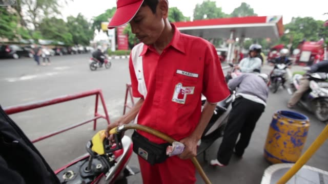 various shots an attendant refuels customers motorcycles at a pt pertamina gas station in jakarta indonesia on tuesday sept 3 2013 a pt pertamina gas... - gas station attendant stock videos and b-roll footage