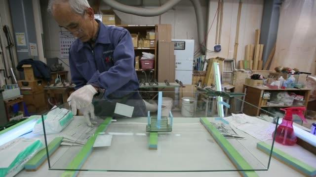 vídeos y material grabado en eventos de stock de various shots an employee assembles a showcase with glass sheets at the nishio glass & mirror co factory in tokyo, japan, on wednesday, feb 26 an... - tape measure