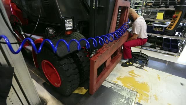 various shots an employee positions a mast and secures it to a diesel engine forklift truck, then assembles its hydraulic system at the linde... - pgaイベント点の映像素材/bロール