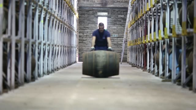 Various shots an employee rolls casks of The Glenlivet single malt whisky produced by Pernod Ricard SA through a storage warehouse at the companys...