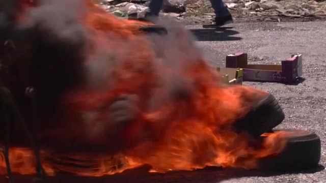 vídeos de stock, filmes e b-roll de various shots as students from birzeit university block road with burning tires and trash containers during a solidarity demonstration for... - ramallah
