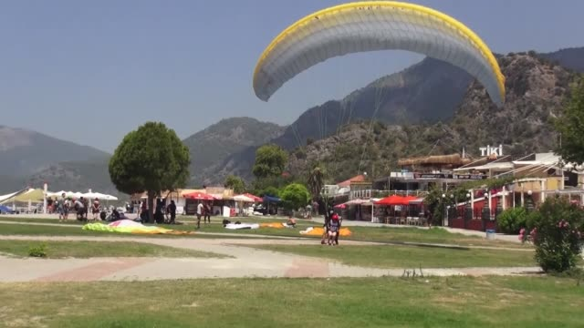 various shots as turkish paragliders perform in fethiye district of southwestern mugla province by observing coronavirus restrictions with wearing... - mugla province stock videos & royalty-free footage