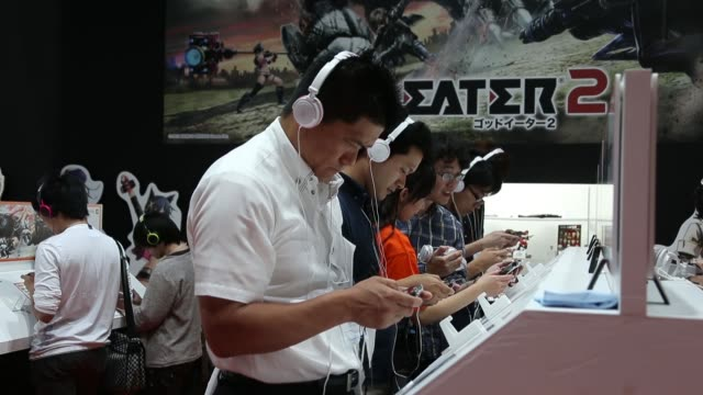 vídeos de stock, filmes e b-roll de various shots attendees play video games on handheld game players at the tokyo game show 2013 at makuhari messe in chiba, japan, on thursday, sept.... - game show