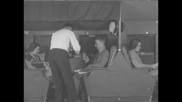 various shots biplane in air / cabin interior with attendant serving passengers / cu woman eating sandwich can see words american airways on side /... - bathrobe stock videos & royalty-free footage
