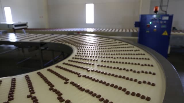 various shots chocolate confectionery passes along a conveyor belt during production at the rossiya chocolate factory operated by nestle sa in samara... - chocolate factory stock videos & royalty-free footage