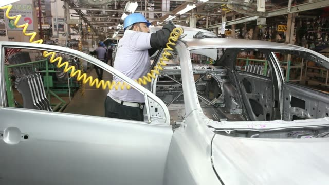 Various shots employees of Indus Motor Co the Pakistan affiliate of Toyota Motor Corp work on the Toyota Corolla assembly line of the company's plant...