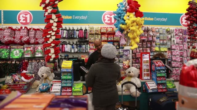 Various shots employees serve customers at the checkout counters inside a Poundland discount store operated by Poundland Group Plc in the Fulham...
