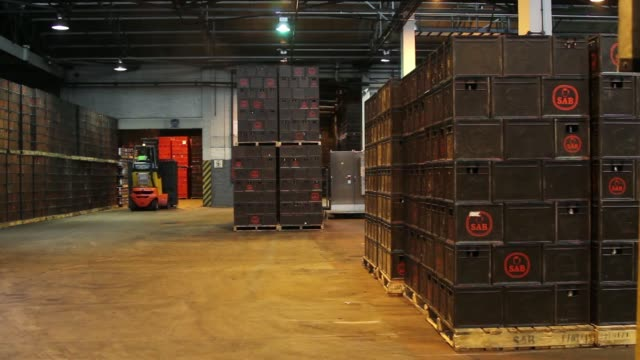 various shots employees use fork lift trucks to move pallets of beer crates to a waiting delivery lorry in the bottling plant at the sabmiller plc... - beer cap stock videos & royalty-free footage