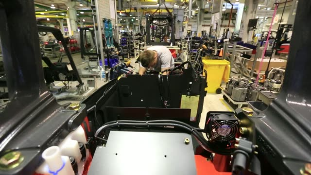 vídeos de stock, filmes e b-roll de various shots employees work on a linde e25 electric forklift truck on the vehicle production line at the linde material handling gmbh factory a unit... - produto interno bruto