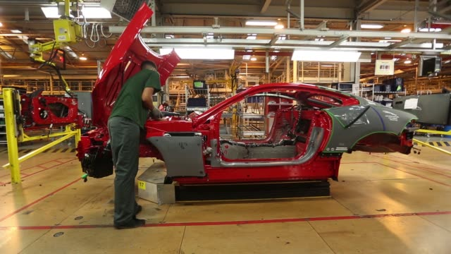 various shots employees work on a red luxury f type jaguar automobile, produced by jaguar land rover plc, a unit of tata motors ltd, as it travels... - workbench stock videos & royalty-free footage