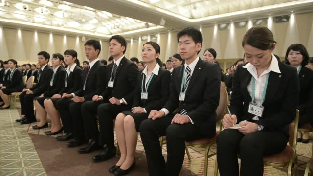 various shots female seven i holdings co new employees attend an initiation ceremony in tokyo japan on thursday march 13 new employees applaud during... - 雇用と労働点の映像素材/bロール