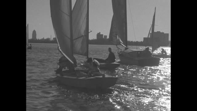 various shots from moving boat of people sailing sailboats / shot on board sailboat of two women sailing boat / shot from moving boat of people... - capsizing stock videos and b-roll footage