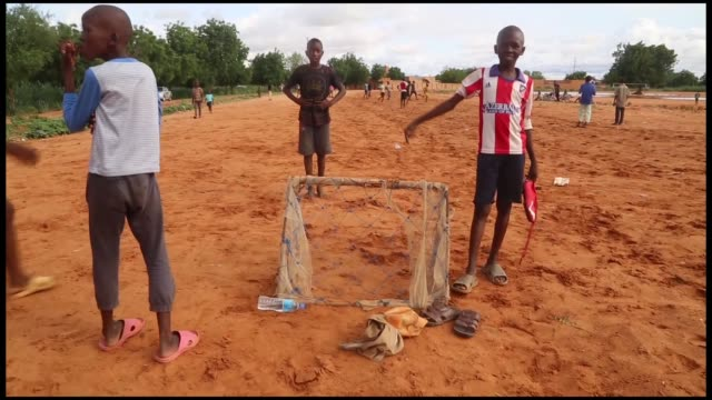 stockvideo's en b-roll-footage met various shots from nigerien kids playing soccer at a racetrack because of not having a proper soccer field on august 27 2018 in niamey - human interest