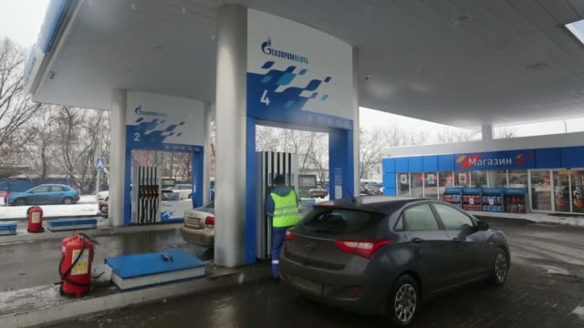 various shots fuel attendants motorists and vehicles on the forecourt of a gas station operated by oao gazprom neft on a snowy day in moscow russia... - gas station attendant stock videos and b-roll footage