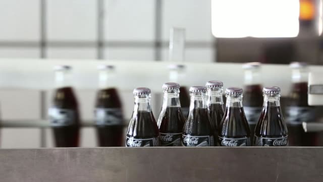 various shots glass bottles of coca cola light also known as diet coke move along the production line after filling at the lanitis bros ltd bottling... - bottling plant stock videos & royalty-free footage