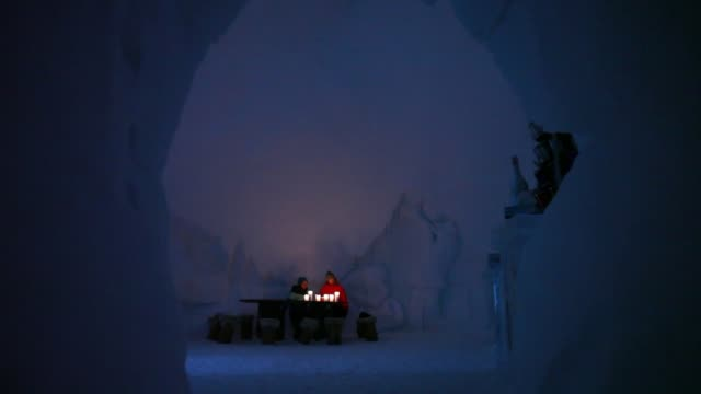 Various shots guests sit illuminated by candle in the lobby of the igloo hotel operated by IgluDorf GmbH on the Parsenn mountain in this arranged...