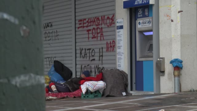 vídeos y material grabado en eventos de stock de various shots homeless greek man lying asleep on pavement by atm cashpoint and shuttered shops covered in graffiti, people walking past homeless in... - crisis