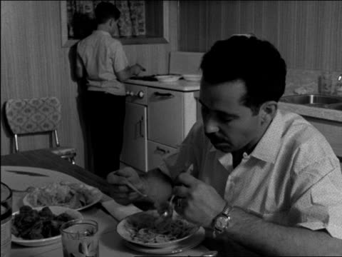 various shots inside italian canadian household - frontal mcu and over-the-shoulder shot of man eating spaghetti, to boy at stove cooking hot dog... - italienischer abstammung stock-videos und b-roll-filmmaterial