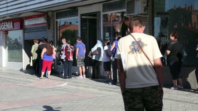 various shots jobseekers queue outside the shuttered entrance to an employment center shortly before opening in madrid spain on wednesday july 23... - unemployment stock videos and b-roll footage