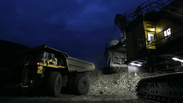 various shots lights illuminate a shovel loader as it picks up and deposits excavated rock into trucks during night mining operations in the open pit... - mine stock videos & royalty-free footage