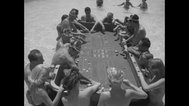 various shots men and women in las vegas sands hotel swimming pool at tables playing craps in the 1950s, other gambling tables in pool in bkgd /... - craps stock videos & royalty-free footage