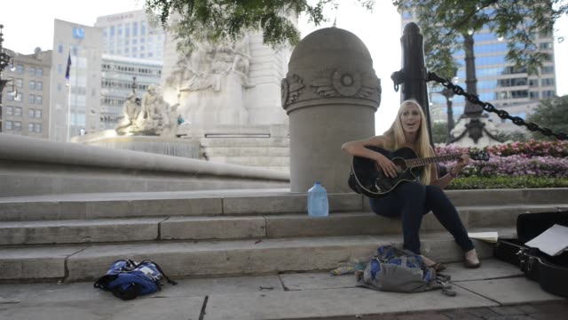 vídeos de stock, filmes e b-roll de various shots of a blonde female street musician playing the guitar as people walk by in indianapolis indiana - dedilhando instrumento