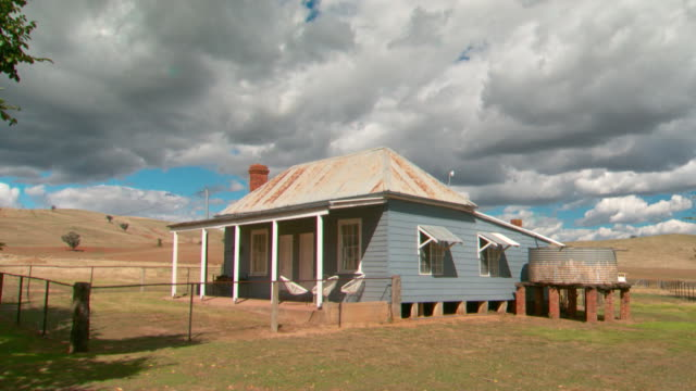 various shots of a charming weatherboard farm workers cottage with a corrugated iron water tank and brick chimney, wood stack and easy chairs on... - farmhouse stock videos & royalty-free footage