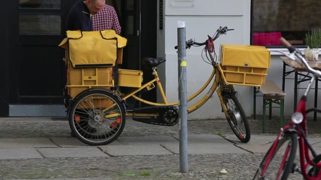 vídeos de stock e filmes b-roll de various shots of a deutsche post postal worker riding a yellow bike along his delivery route in berlin, germany, a courier looks through a pile of... - letterbox
