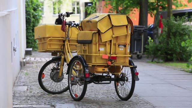 various shots of a deutsche post postal worker riding a yellow bike along his delivery route in berlin germany a yellow deutsche post delivery bike... - postangestellter stock-videos und b-roll-filmmaterial