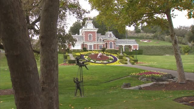 various shots of a disneyworld esque building and floral clock on the neverland ranch property in los olivos, california, a medium shot of a statue... - ネバーランドバレーランチ点の映像素材/bロール