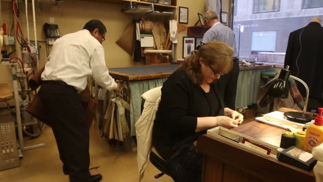various shots of a female tailor manually sewing a pant leg together at richard bennett custom tailors in chicago illinois us - 仕立て屋点の映像素材/bロール