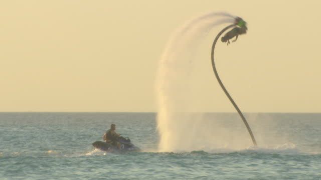 vídeos de stock, filmes e b-roll de various shots of a flyboarder performing beside jetski, camel train passes along beach and in front of campervan in front of brilliant yellow sunset... - cable
