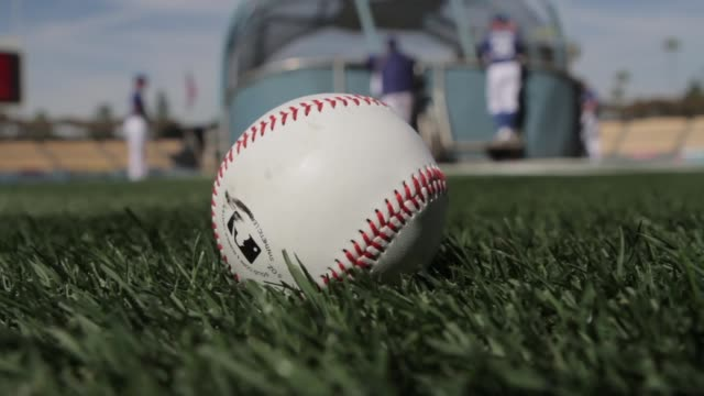 various shots of a major league baseball laying on baseball field in foreground / baseball players practicing in background / rack focus of baseball... - baseballmannschaft stock-videos und b-roll-filmmaterial